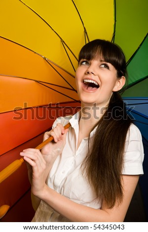 laughing young brunette woman in white blouse with multi-coloured umbrella - stock photo