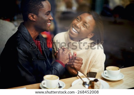 Laughing young couple in cafe, having a great time together, view through cafe window, romantic couple having fun together, best friends smiling sitting in cafe, view through cafe window - stock photo
