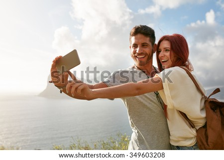 Laughing young couple on holidays making selfie with mobile phone. Young couple by the bay taking a selfie portrait with smart phone.