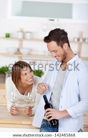 Laughing young couple starting to drink a red wine at home - stock photo