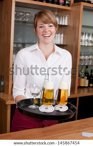 Laughing young female waitress or bartender serving drinks in a bar carrying a tray with beer and mineral water - stock photo