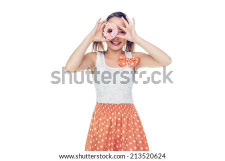 Laughing young girl holding a ring doughnut to her eye and looking through the middle, over white with copyspace - stock photo