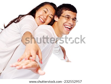 Laughing young interracial couple in love having fun posing as flying on isolated white background