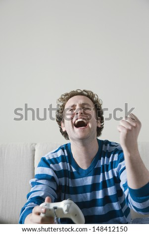 Laughing young man holding video game console on sofa - stock photo