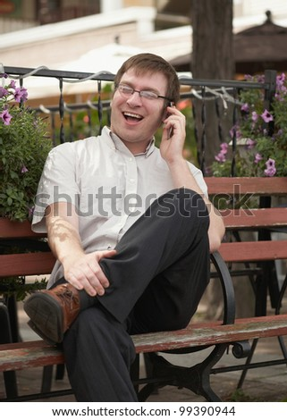 Laughing young man on phone conversation outside - stock photo