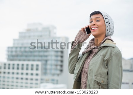 Laughing young model in winter clothes answering her phone outside on a cloudy day - stock photo