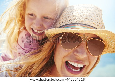 Laughing young mother in a trendy hat and sunglasses giving her little daughter a piggy back outdoors in the summer sunshine with the breeze blowing their long blond hair, close up head shot - stock photo