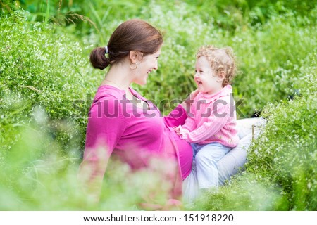Laughing young pregnant mother playing with her one year old baby daughter in a beautiful garden - stock photo