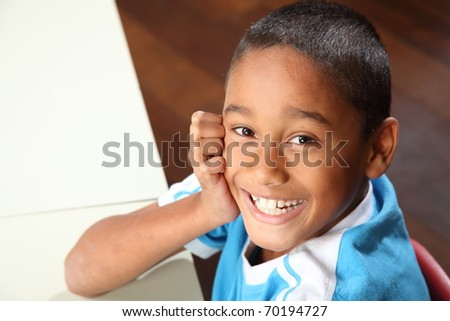 Laughing young school boy age nine sitting to his classroom desk