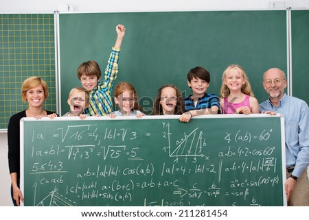 Laughing young schoolchildren posing with their two teachers holding a chalkboard full of mathematical equations - stock photo