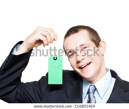 Laughing young store sales man holding up a blank price tag for your text or contact details in a depiction of sale and commission - stock photo
