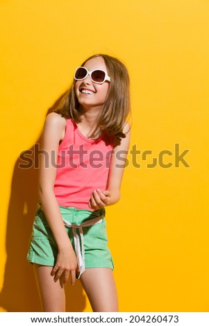 Laughing young summer girl looking away. Three quarter length studio shot on yellow background.