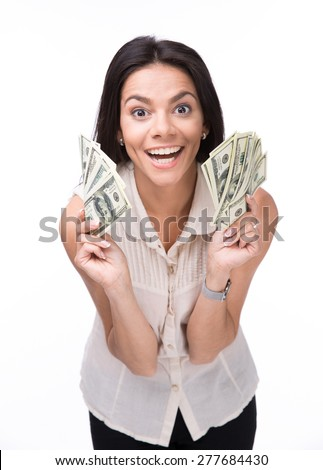 Laughing young woman holding money over white background and looking at camera - stock photo