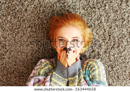 Laughing young woman lying on the carpet at home - stock photo