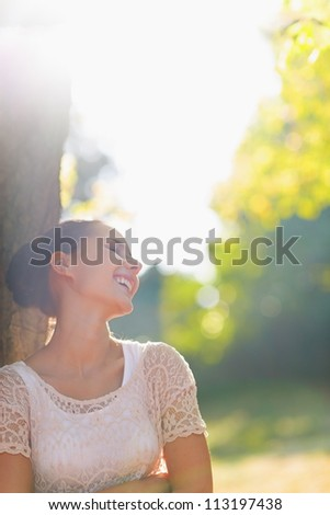 Laughing young woman relaxing in forest - stock photo