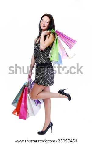 Laughing young woman standing isolated on white with color bags