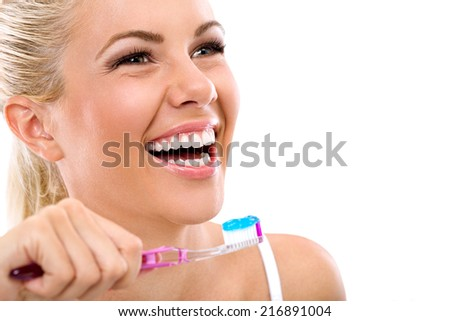 Laughing young woman with healthy teeth holding a tooth-brush - stock photo