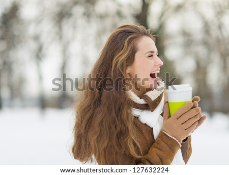Laughing young woman with hot beverage in winter park