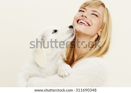 Laughing young woman with pet puppy, studio - stock photo