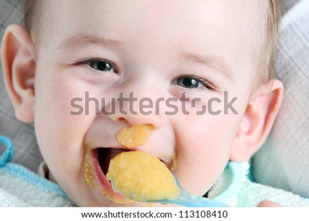 Laughter baby boy eating vegetable mash - stock photo