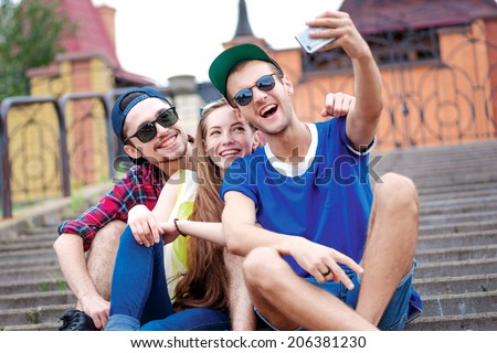 Laughter of friends. Young friends have fun together on the street and smile at each other. Funny guys make Selfie - stock photo