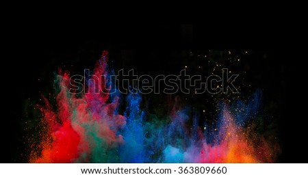 Launched colorful powder, isolated on black background - stock photo