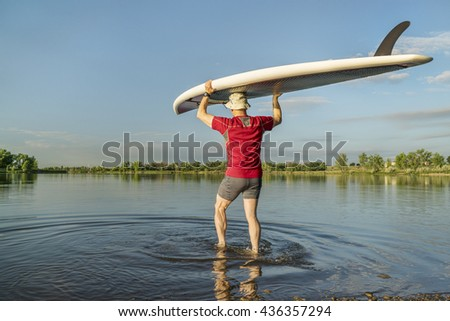 launching stand up paddleboard on a calm  lake in northern Colorado with an early summer scenery - stock photo