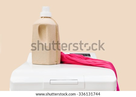 Laundry background. Top loading washing machine with natural organic detergent and colorful clothing isolated on beige background.  - stock photo