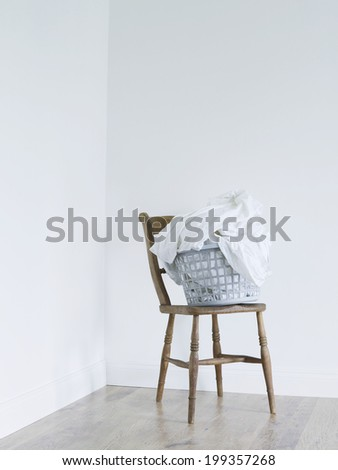 Laundry basket on chair in room - stock photo
