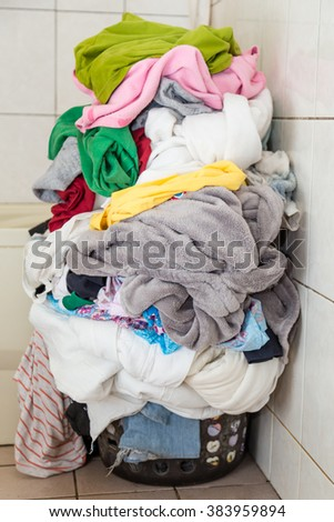 Laundry basket overflowing with dirty clothes and blankets - stock photo