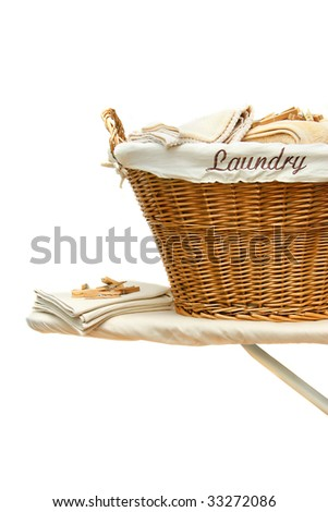 Laundry basket with towels on ironing board against white background - stock photo
