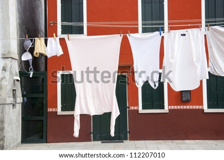 Laundry hanging out of a typical house of Burano Island - Venice,  Italy - stock photo
