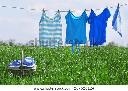 Laundry line with clothes in spring field - stock photo