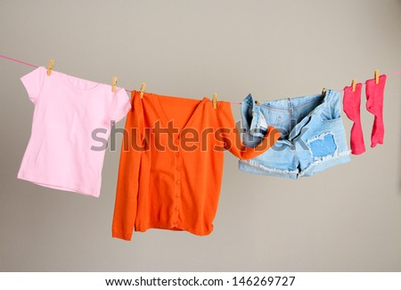 Laundry line with clothes on wall background