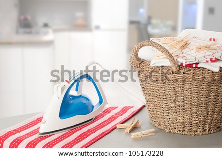 Laundry on ironing board in kitchen setting - stock photo