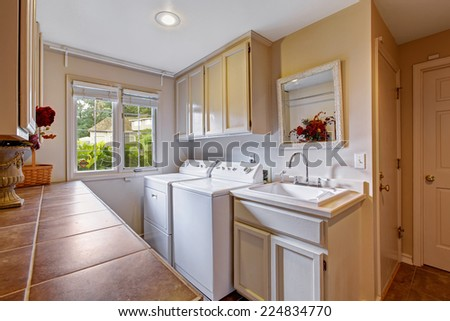 Laundry room with window and standard appliances. Room has cabinets and sink