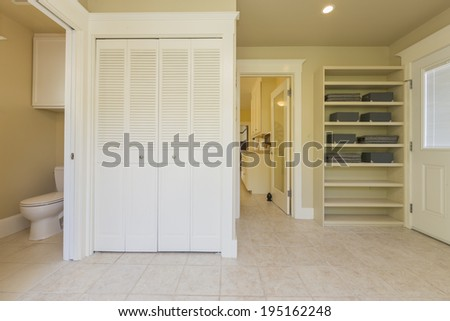 Laundry room with wood cabinets, bathroom and tiled floor. - stock photo