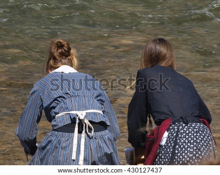 laundry women cleaning clothes in the shore of a river