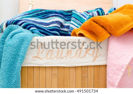 Laundry wood basket with colored towels