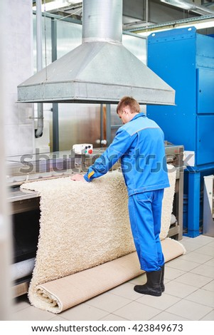 Laundry worker in the process of working on the automatic machine for drying carpets