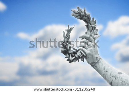 Laurel Wreath hand held by a bronze statue on sky background with copy space