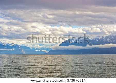 Lausanne quay of Geneva Lake and mountains in winter Ouchy in Switzerland. Lausanne is a city in Switzerland. Ouchy is a port and popular lakeside resort in Lausanne.