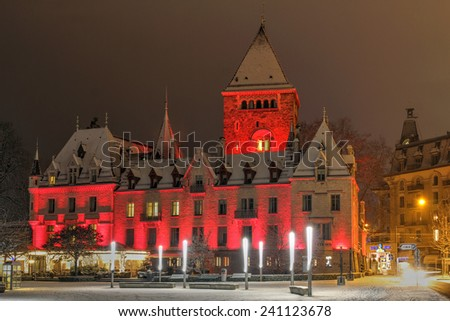 LAUSANNE, SWITZERLAND - DECEMBER 29: Night scene of the Chateau d'Ouchy in Lausanne, Switzerland with a winter look after a very recent snowfall on the evening of December 29, 2014. - stock photo