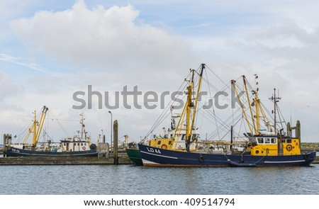 Lauwersoog, The Netherlands - August 20, 2012: Two fishing vessels in the harbor in the province of Groningen.