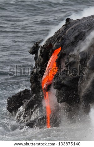 Lava flow flows into the sea in Hawaii - stock photo