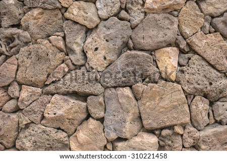 Lava rock exterior wall with pattern/texture in tones of brown,tan,red, and gray/grey. - stock photo