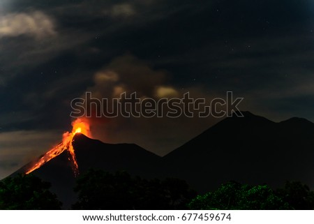 Lava spurts from erupting Fuego volcano next to Acatenango volcano just before dawn near Antigua, Guatemala, Central America