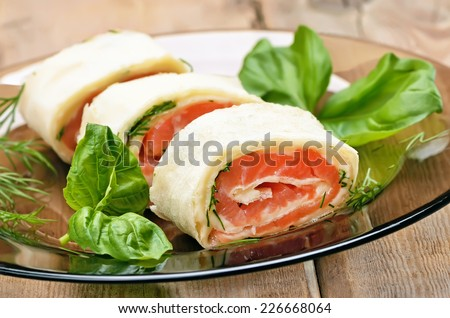 Lavash rolls with salmon and cheese on glass plate on wooden table - stock photo