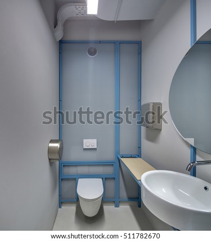 Lavatory in a loft style with the glowing lamps and gray walls. There is a metal mesh partition, a white sink with a faucet and a mirror, a white toilet, tissue dispensers and a wooden tabletop.