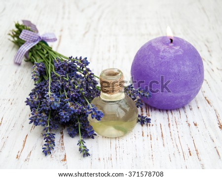 Lavender and massage oil on a wooden background - stock photo